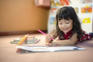 Little girl writing on a paper