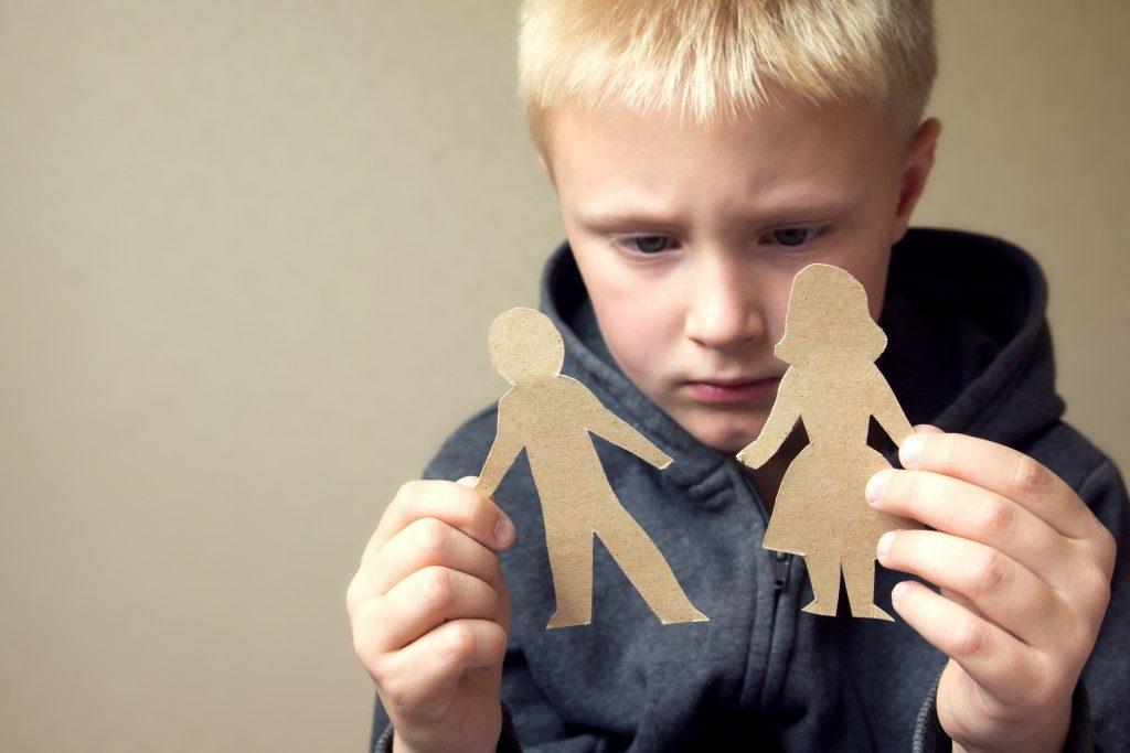 Child holding paper dolls divorce concept