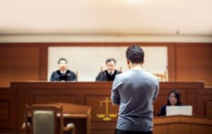 court case with defendant, judges, and stenographer