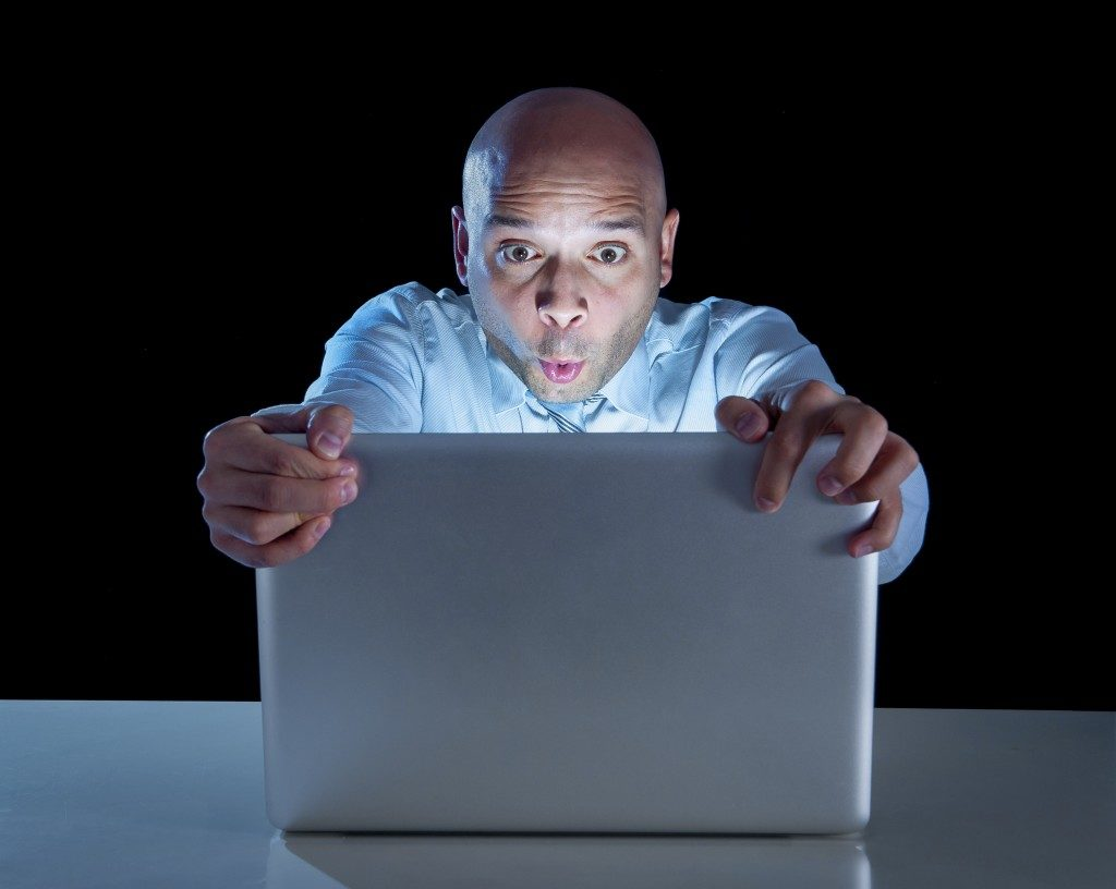 man playing on laptop