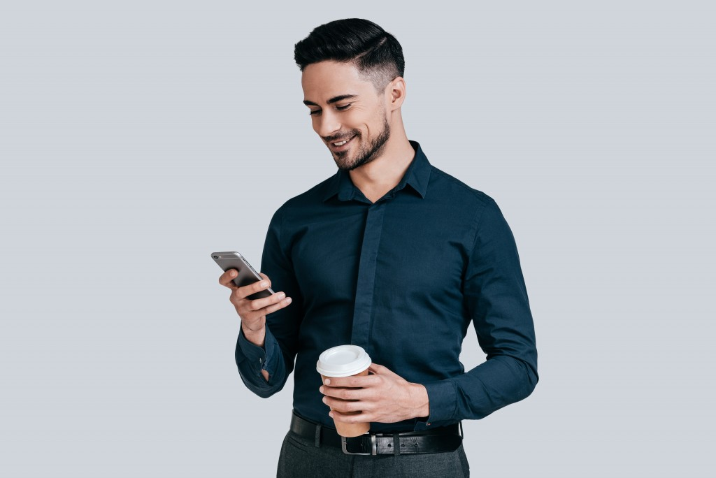 man smiling while using his phone