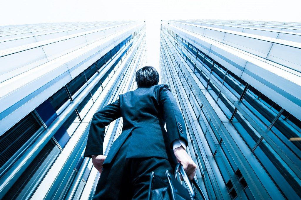 low angle shot of business man staring at the highrise buildings