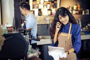 Asian barista talking order by phone in her shop