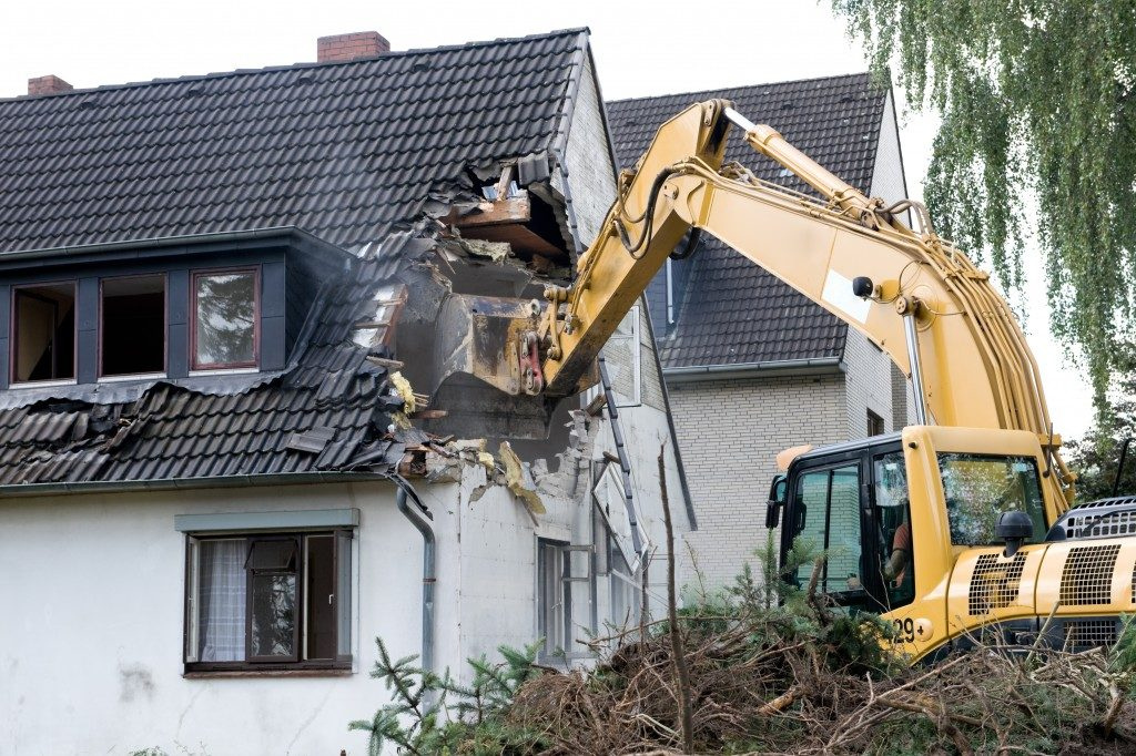 Bulldozer demolishing houses for reconstruction