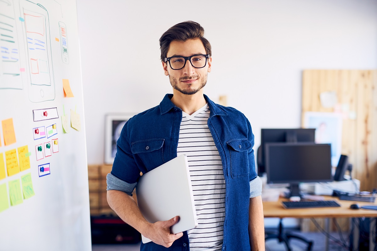 man carrying laptop at the office
