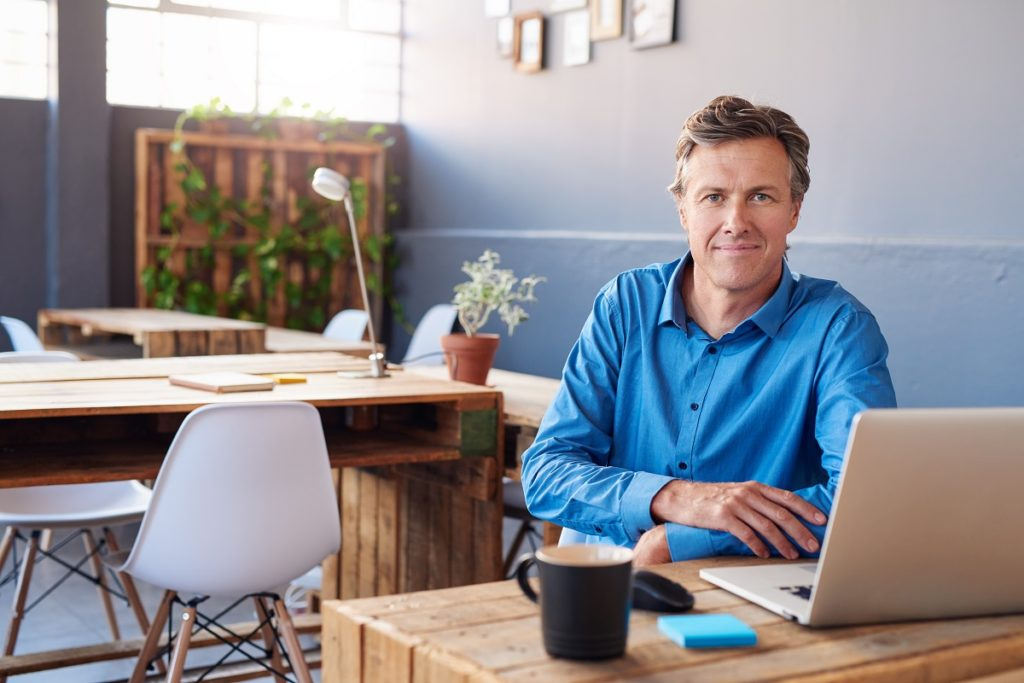 man working with his laptop and coffee at a trendy office