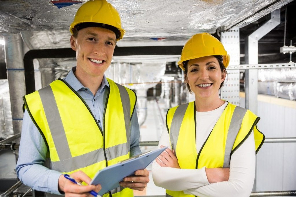 Man and woman worker wearing fluorescent vests