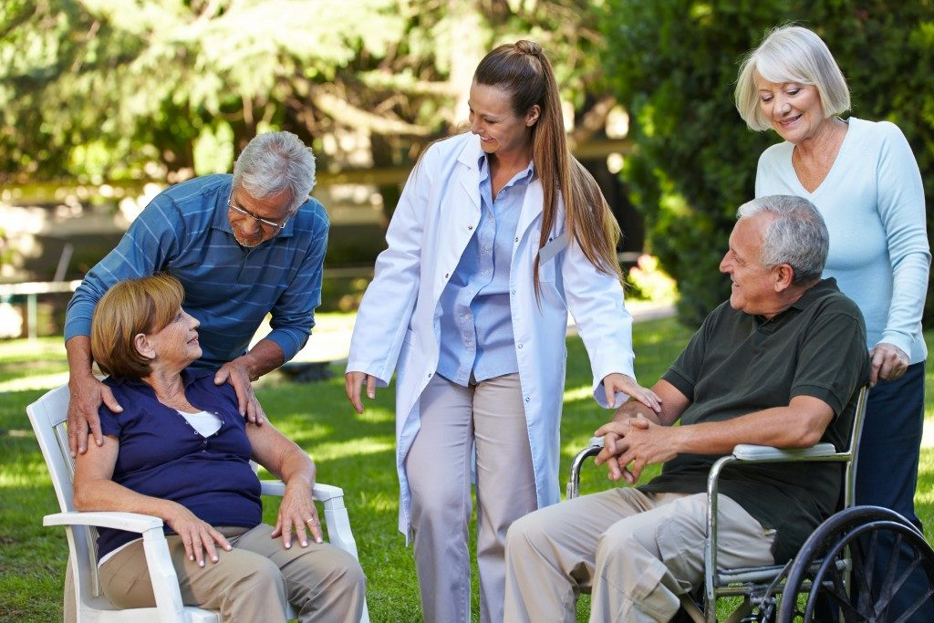 Many seniors relaxing in a park of a nursing home with geriatric nurse