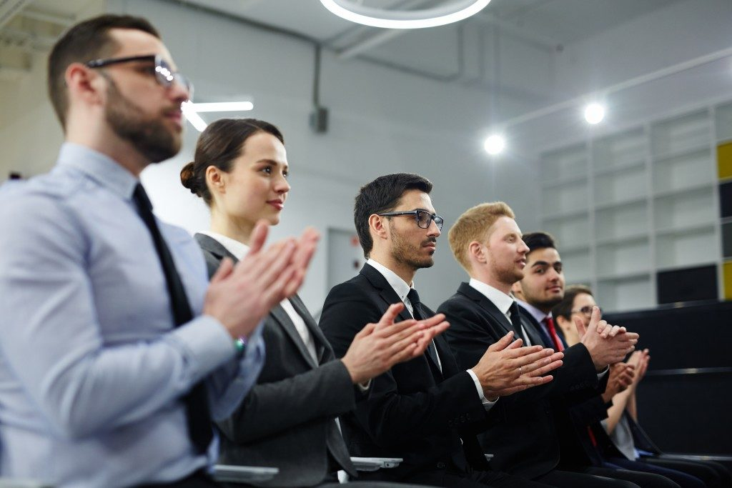 Row of managers clapping hands after report