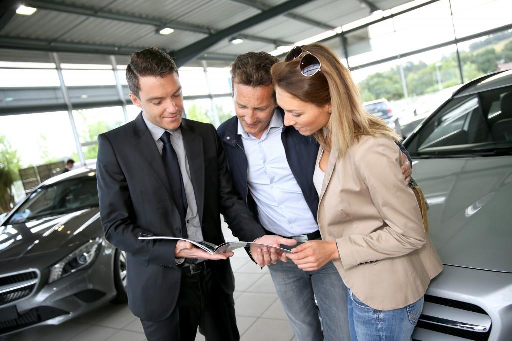 Car salesman talking to a couple
