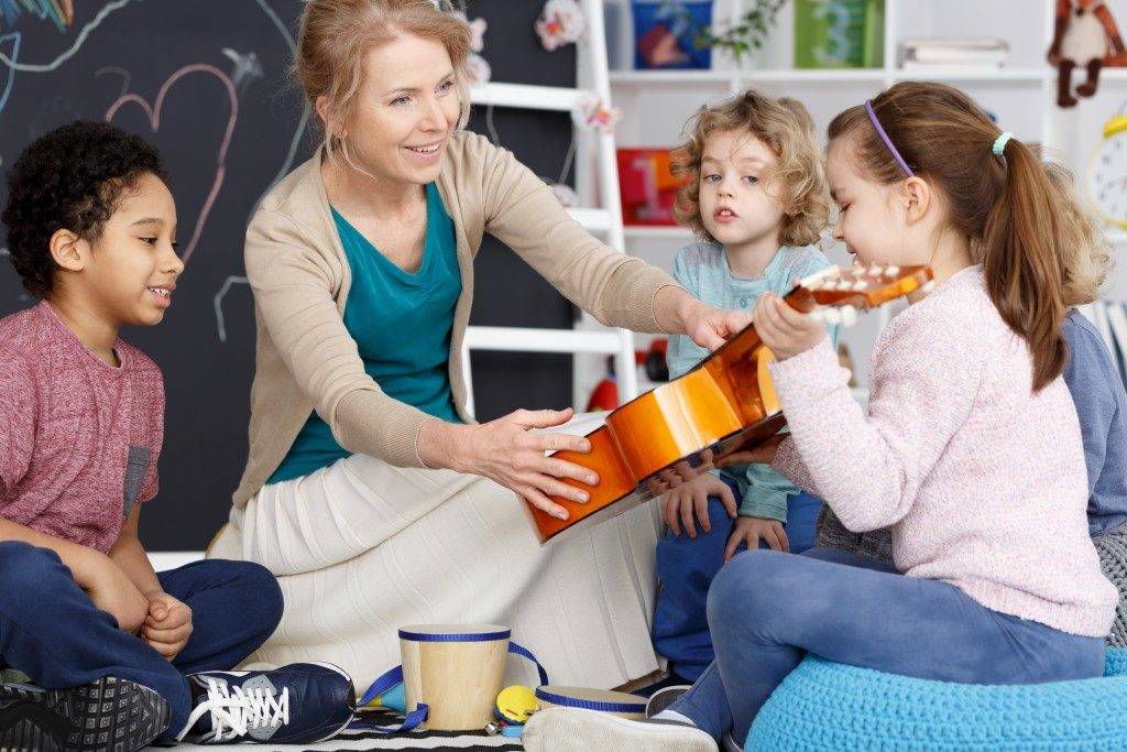 teacher handing out music instrument to preschooler